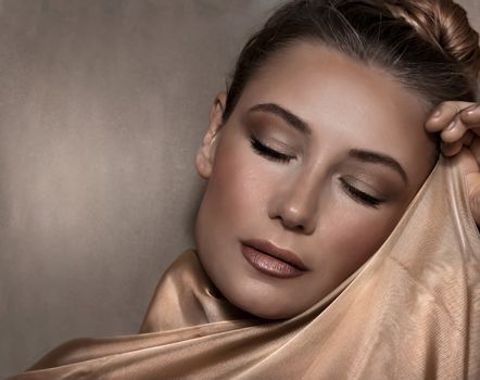 Closeup Portrait of a Beautiful Woman with Evening Makeup Wrapped in a Golden Silk Shawl over Beige Background. Luxury Fashion Look.