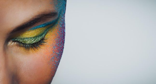 Closeup Photo of a Face Part of a Beautiful Girl Over Clean Background. Young Woman with Festive Colorful Makeup. Photo with Copy Space.