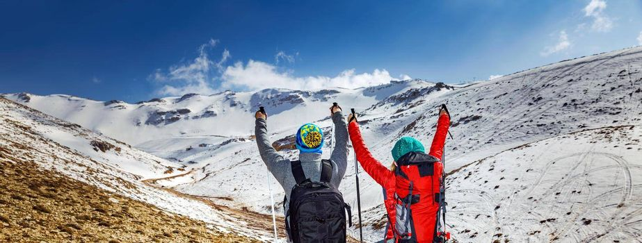 Two Cheerful Hikers Walking in the Snowy Mountains with Trekking Poles. Romantic Vacation. Active Winter Holidays.