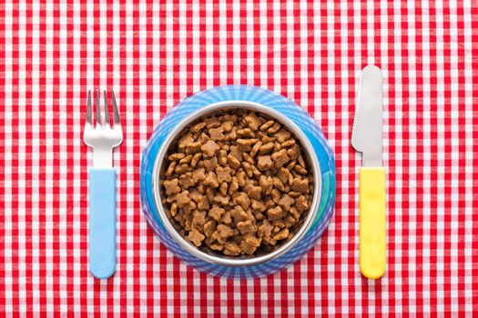 dog food bowl with knife and fork on tablecloth,full of dry food for pets