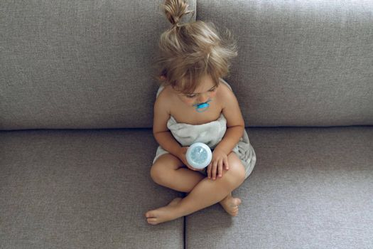 Cute Little Baby With Pleasure Spending Time at Home. Sitting on the Couch Preparing for a Meal. Baby Milk Formula. Healthy Organic Babies Nutrition.