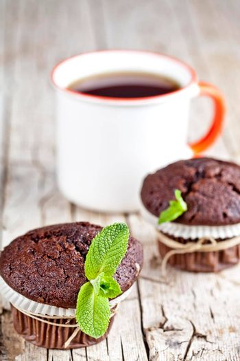 Fresh dark chocolate muffins with mint leaves and cup of tea on rustic wooden table background.