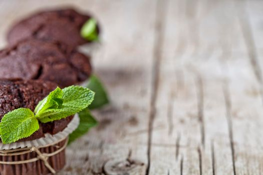 Chocolate dark muffins with mint leaves closeup on rustic wooden table. With copy space.