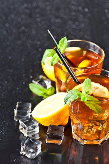 Two glasses with cold traditional iced tea with lemon, mint leaves and ice cubes on wet black background.