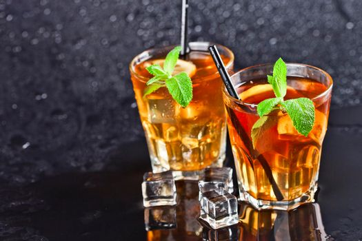 Two glasses with cold traditional iced tea with lemon, mint leaves and ice cubes on wet black background. With copy space.