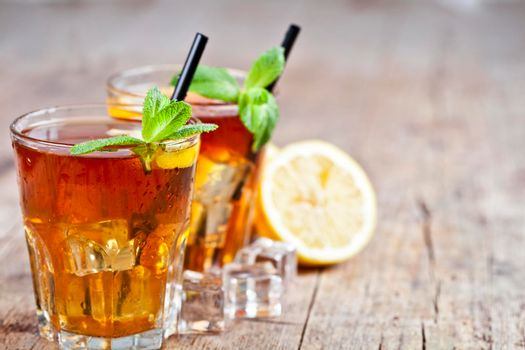 Cold iced tea with lemon, mint leaves and ice cubes in two glasses on rustic wooden table background. With copy space.