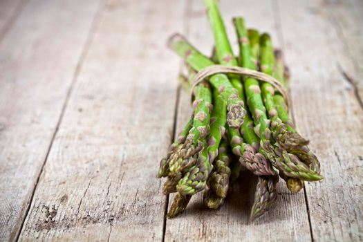 Bunch of fresh raw garden asparagus on rustic wooden table background. Green spring vegetables. Edible sprouts of asparagus. With copy space.