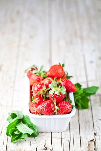 Fresh red strawberries in white bowl and mint leaves on rustic wooden background. Healthy sweet food, vitamins and fruity concept.