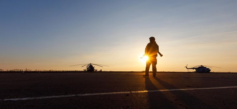 MARIUPOL, UKRAINE - Nov. 16, 2017: Silhouette of a military man with a machine gun in a combat post against the helicopters and sunset sky during festivities on occasion of the Day of Naval Infantry