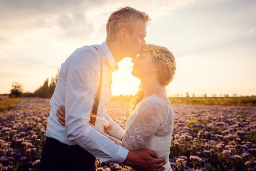 Bridegroom kissing his bride during romantic wedding in the village in a romantic setting