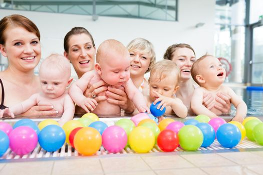 Group of moms and their little babies at baby swimming lesson