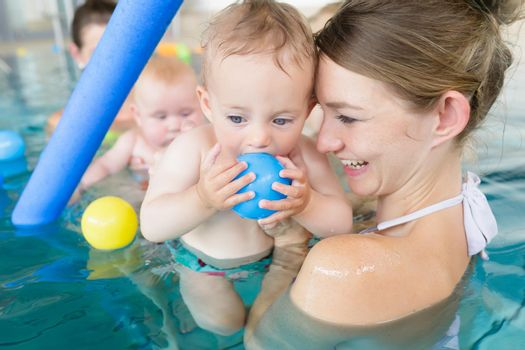 Mothers and their kids having fun at baby swimming lesson between lots of water balls