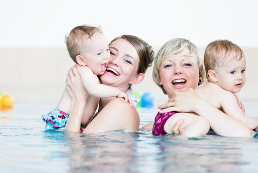 Mothers and their little babies having fun at infant swimming class