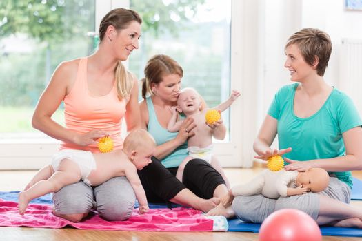Young women practicing massage for their babies in mother-child class