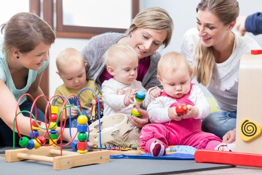 Three dedicated and happy young mothers sitting together on the floor, while watching their babies playing with safe multicolored toys at a modern playground for infants