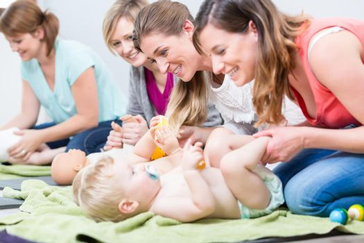 Group of cheerful women learning to take care of their babies during parenting class for young mothers in a contemporary club for moms