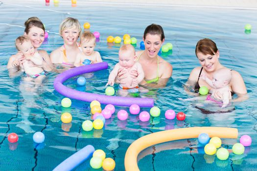 Moms and their newborns playing together with balls and pool noodles at infant swimming class