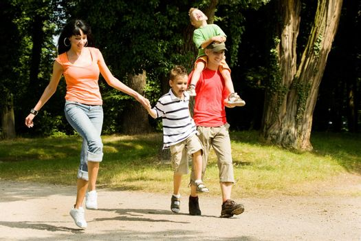 Family with two kids having a walk in the park (focus is on the boy in front!)
