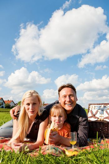 Family - father, mother and daughter child - having a picnic on a green meadow on a beautiful and bright summer day