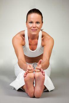 Young woman in a yoga position (Paschimottanasana)
