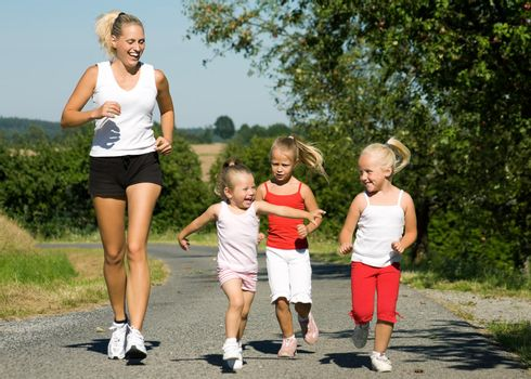 A young mother jogging with her three little daughters