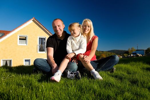 Young family sitting in the sun on the lawn in front of their new home