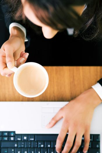 A woman (just hands) at her workplace having a double espresso (focus on hand and cup)