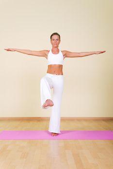 Young woman in a yoga position (Nata Rajasana)