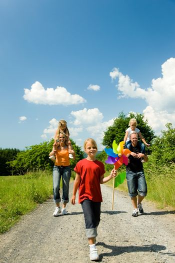 Family having a walk down a path on a sunny day under a perfect blue sky (focus is only on the girl in front!)
