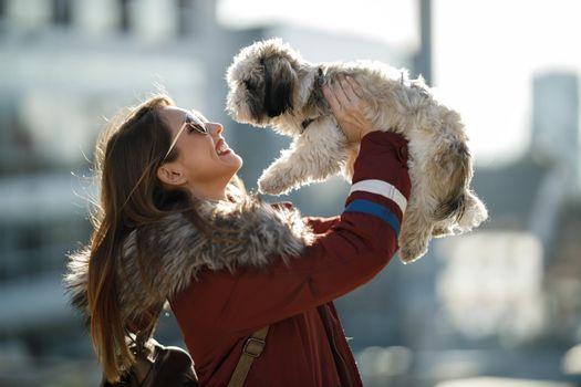 Portrait of a smiling woman having fun with her cute Shih Tzu dog outdoor.