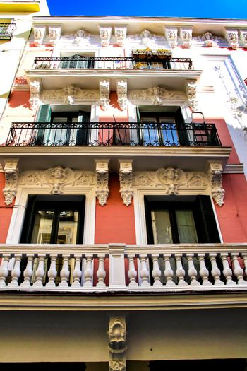 Old colorful and beautiful facades with vintage streetlight in Madrid streets in Spring.