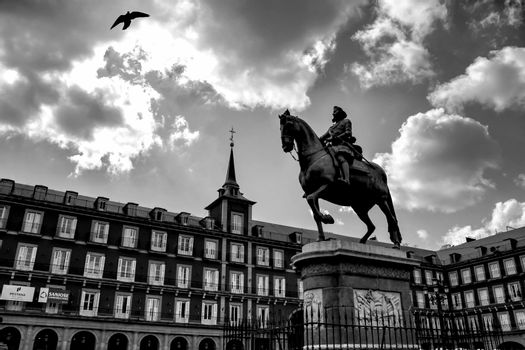 Beautiful equestrian statue of Felipe III in the main square in Madrid called Plaza Mayor with its majestic facades in a sunny day of Spring