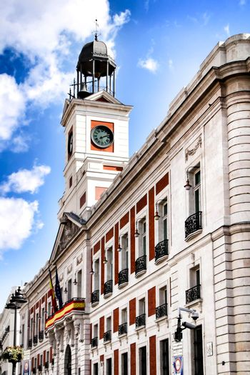Beautiful perspective of the clock tower of the main square in Madrid called Puerta del Sol in a sunny day