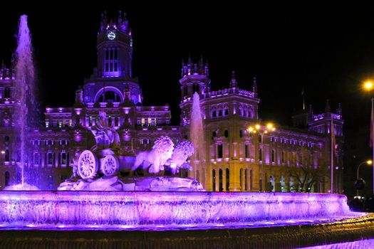Beautiful City Hall of Madrid and Cibeles fountain illuminated in purple in the International Women's Day