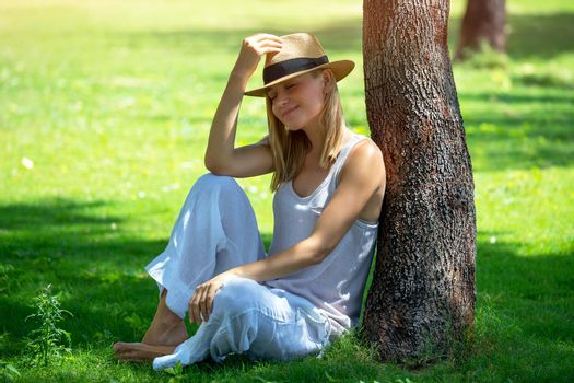Beautiful Girl with Closed Eyes Wearing Stylish Sun Hat in the Park. Resting Near the Tree on Fresh Green Grass. Happy Carefree Spring and Summertime