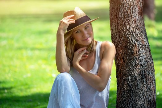 Happy Nice Female Resting Outdoors. Stylish Girl Spending Leisure Time in the Park. Peaceful Summer Travel and Vacation.