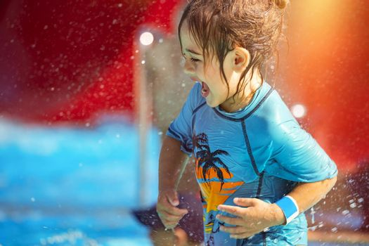 Cheerful Little Boy Having Fun in Waterpark on the Beach Resort. With Pleasure Making Water Splashes. Happy Summer Holidays.