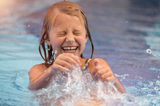 Portrait of a Cute Little Girl Having Fun and Splashing in the Pool. Spending Summer Weekend in Aquapark. Happy Summer Holidays. Carefree Childhood.