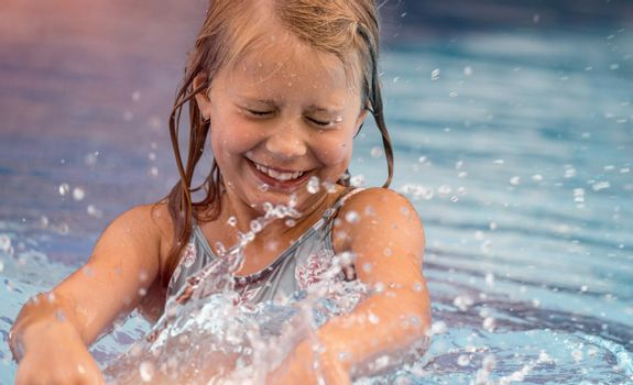 Portrait of a Little Smiling Girl Having Fun and Splashing in the Pool. Spending Summer Weekend in Aquapark. Happy Summer Holidays.