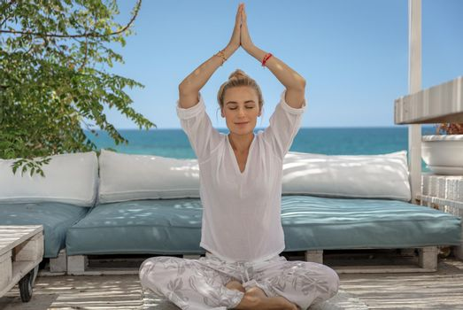 Nice Female Doing Yoga Outdoors. Sitting in the Beach Chalet in Lotus Pose and Meditating. Enjoying Peaceful Summer Vacation on the Beach Resort.