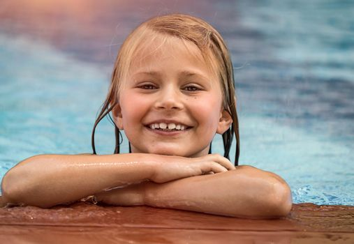 Portrait of a Cute Little Girl in the Pool. Happy Smiling Child Having Fun on the Beach Resort in Sunny day. Enjoying Summer Holidays.