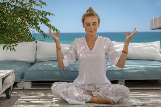 Beautiful Woman Sitting in the Beach House in Lotus Pose and Meditating with Closed Eyes. Yoga Outdoors. Concentration and Soule Balance Concept.