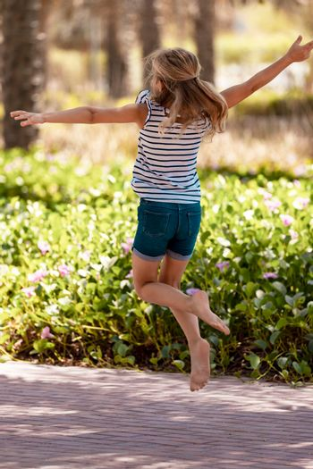 Happy Little Girl Having Fun in the Park. Cheerful Child Playing Games and Jumping on the Way. Carefree Childhood. Enjoying Summer Holidays.