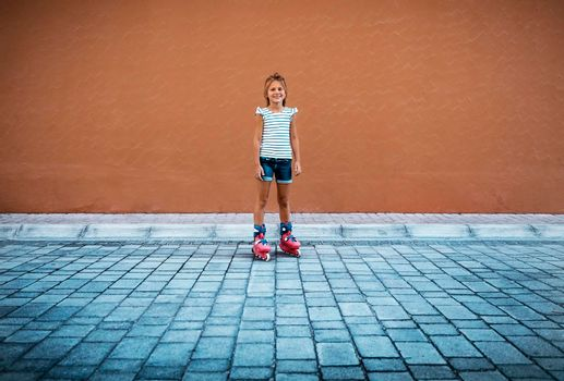 Cute Happy Little Girl Rollerblading in the Yard. Having Fun Outdoors. Perfect Summertime Recreation. Healthy Sportive Summer Holidays Concept.
